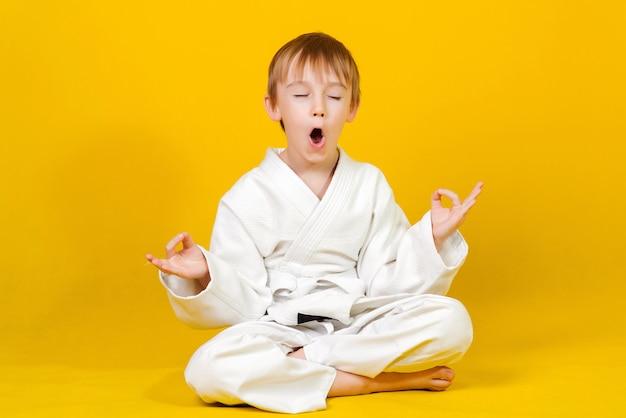 黄色の上に座っている白い着物姿の少年