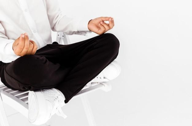 Мальчик в белой рубашке и черных брюках позирует на белом фоне в позе лотоса.