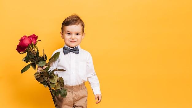 Мальчик в белой рубашке, брюках и галстуке-бабочке держит в руках букет красных роз. подарок маме