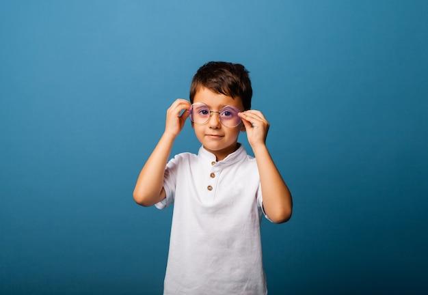 白いtシャツを着た少年は、彼の手に眼鏡を持って、青い背景の上のカメラを見ています。眼鏡をかけた少年。