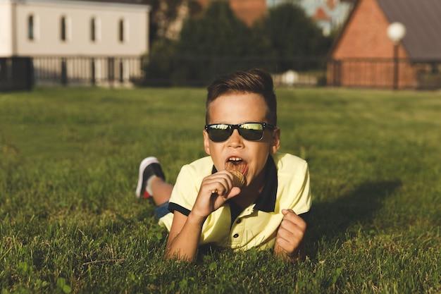 黄色いtシャツを着た少年がアイスクリームを持って草の上に座っています。