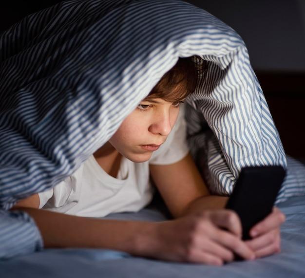 모바일에서 재생하는 침대에서 소년