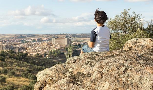 Мальчик в сине-белой рубашке сидит на большом камне спиной и смотрит на пейзаж