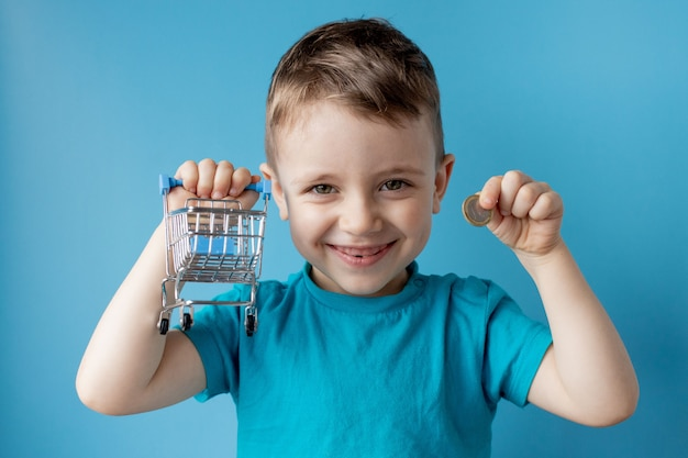 青いtシャツの少年は、ショッピングカートとコインを保持しています。ショッピングと販売のコンセプト。