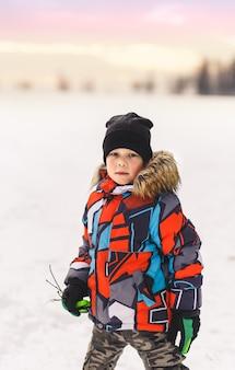 Мальчик в яркой зимней куртке на прогулке