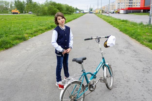 대학 재킷과 모자를 쓴 소년은 녹지와 집이 있는 여름 거리의 아스팔트 도로에 자전거와 함께 서 있습니다.