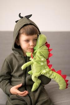 Мальчик в костюме динозавра играет
