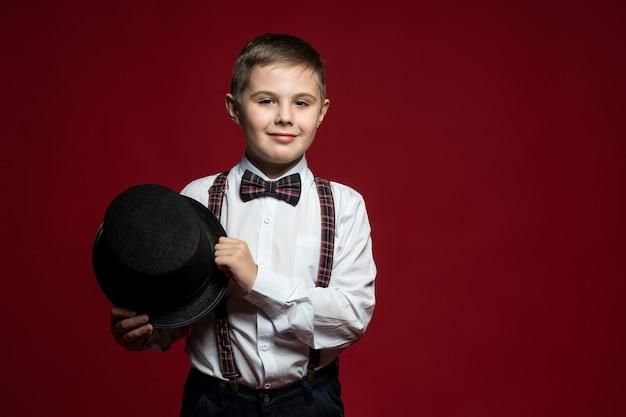 Мальчик в элегантной одежде сидит на железной стремянке у красной стены