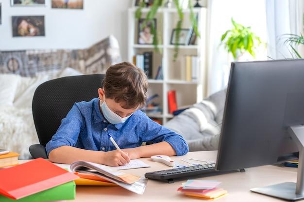 コロナウイルスの検疫中に宿題をして、コンピューターを使用してフェイスマスクの少年