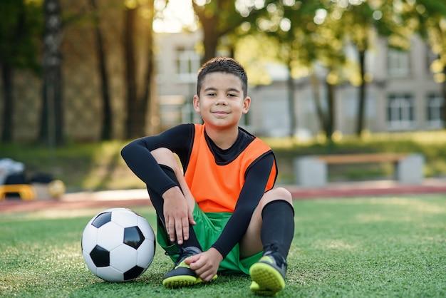 Мальчик в футбольной форме с футбольным мячом после интенсивной тренировки на стадионе