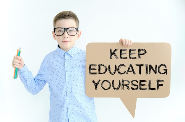 テキスト付きのカードを持っている眼鏡をかけた少年あなた自身を教育し続けてください。