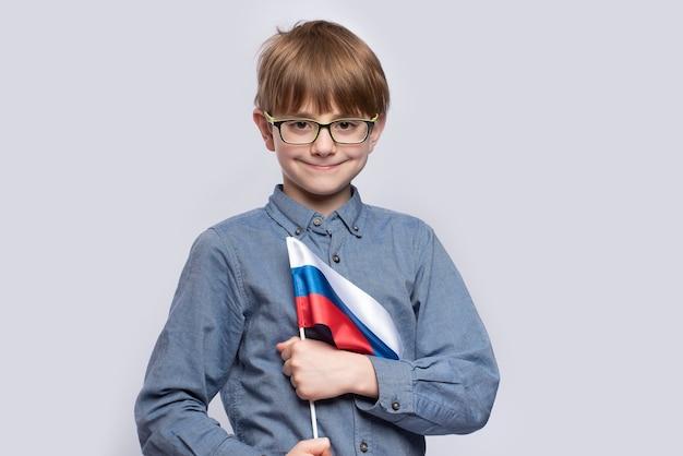 Мальчик в очках держит флаг россии на белом