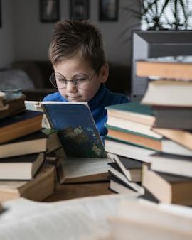 彼の隣に本のスタックで本を読んでいる眼鏡の少年。