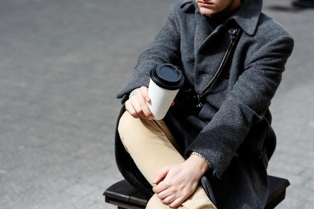 Мальчик в сером пальто держит чашку кофе на коленях, сидя на улице