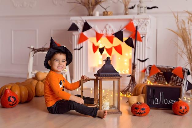 Мальчик в костюме ведьмы на хэллоуин с тыквой