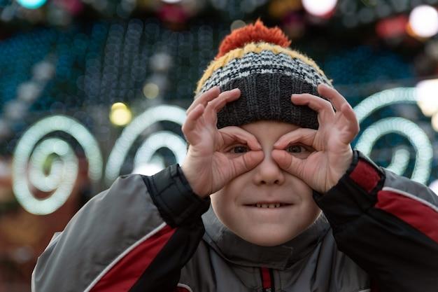 双眼鏡のような形の指を通して見ている帽子の少年。眼鏡のように目の近くで指を持っている子供。クリスマスの飾り