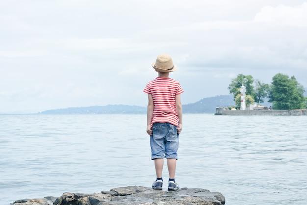 해변에 서있는 모자에 소년입니다. 거리에있는 작은 등대. 뒷면보기