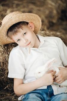 かわいい白うさぎを維持し、笑顔の干し草帽子の少年