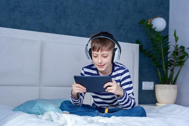 電話で見て遊んでいるヘッドフォンの少年