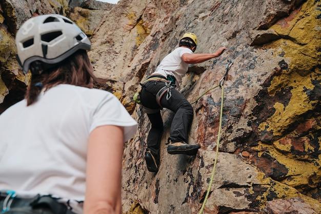 파트너가 지켜보는 동안 등반하는 30대 소년