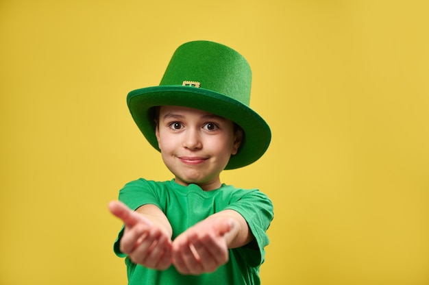 レプラコーンの少年アイルランドの帽子はカメラに彼の手のひらを伸ばします
