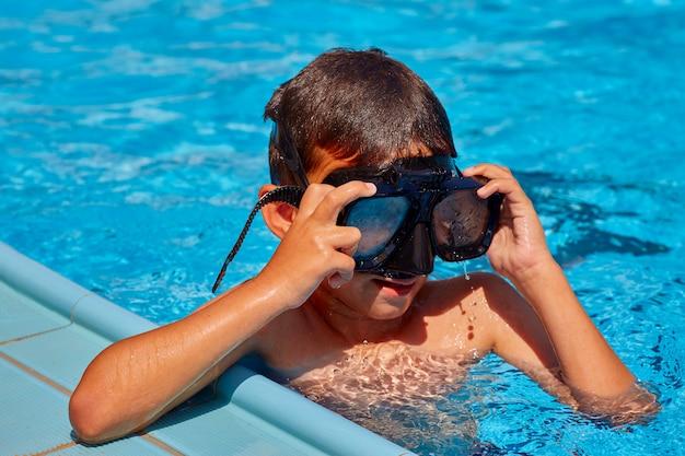 プールで泳いでいるマスクの少年