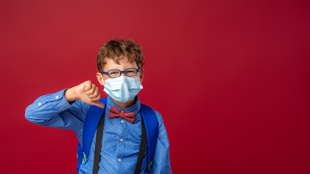 メガネと学校のバックパックが付いているマスクの少年は不承認のジェスチャーを示しています
