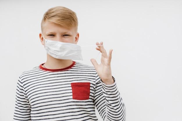 Мальчик в медицинской маске. понятие карантина и защиты от загрязненного воздуха. коронавирус, болезнь, инфекция. карантин и защита от вирусов, гриппа, эпидемии covid-19. . фото высокого качества