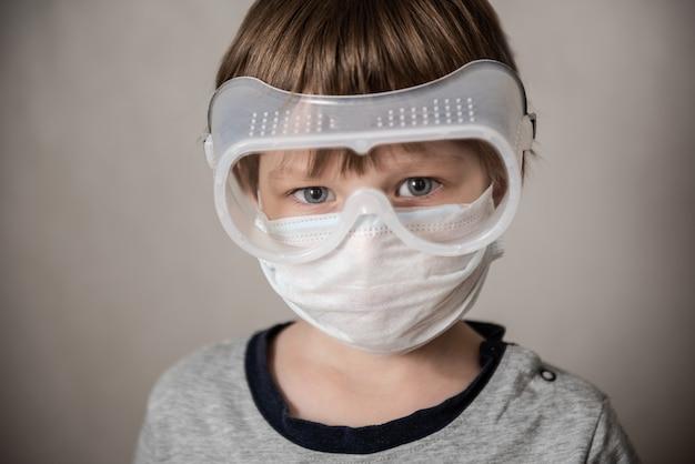 Мальчик в медицинской маске. изоляция коронавируса covid-19, паника. вакцина от нового вируса. отрицательные эмоции