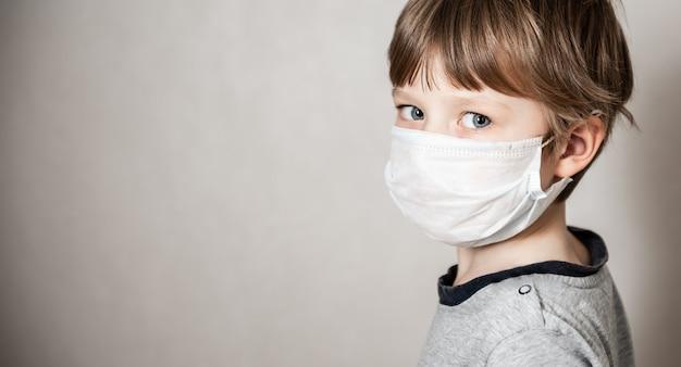 医療マスクの少年。コロナウイルスcovid-19ロックダウン、パニック。新しいウイルスからのワクチン