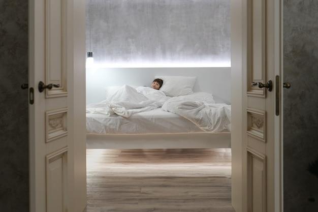 부모 침대에서 소년입니다. 열린 문을 통해 하얀 시트가 보이는 아픈 침대에 있는 아이.