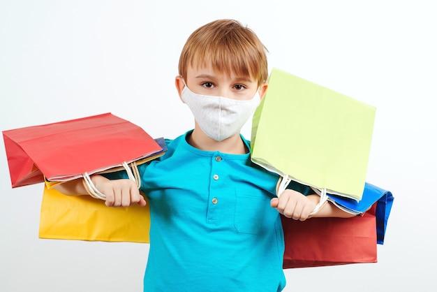 Мальчик в защитной маске, держащей хозяйственные сумки.