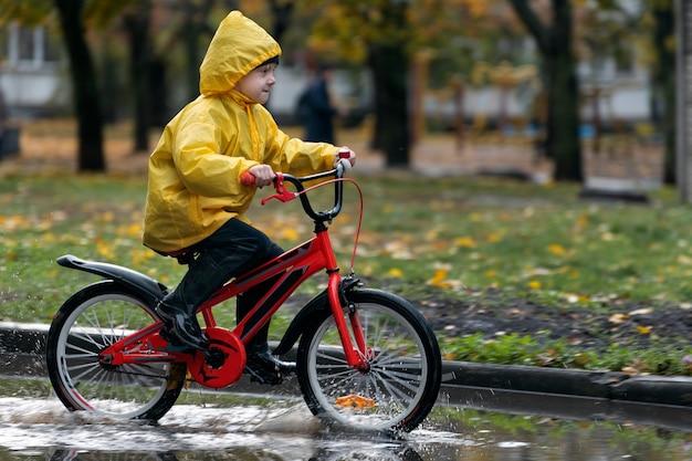 Мальчик в плаще один на велосипеде по лужам. счастливый ребенок едет на велосипеде под дождем.