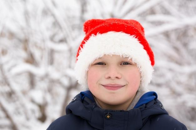 눈 덮인 자연의 배경에 빨간 모자 소년 프리미엄 사진