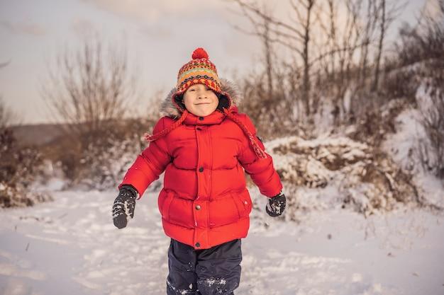 屋外で遊ぶ赤いファッションの服を着た少年