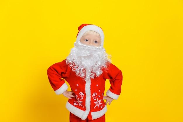 빨간 산타클로스 의상을 입은 소년은 노란색 스튜디오 배경에 서서 손을 엉덩이에 얹고 있다