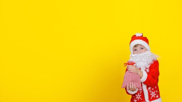 산타클로스 옷을 입고 인조 흰 수염을 가진 소년은 새해 선물이 든 자루를 손에 들고 있다