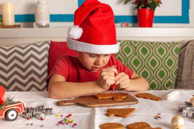 산타클로스 모자를 쓴 소년은 크리스마스를 기다리는 진저브레드를 조심스럽게 장식합니다.