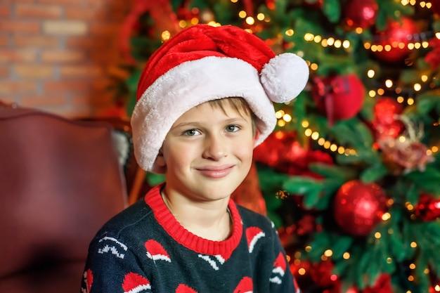 クリスマスツリーの近くの自宅でサンタの帽子をかぶった少年。クリスマスを待っている幸せな子