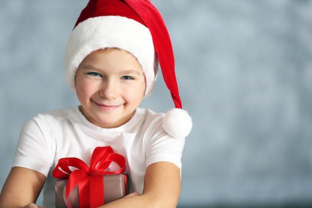 회색 배경에 선물 상자가 있는 산타 모자를 쓴 소년