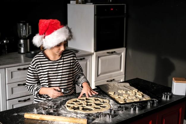サンタの帽子をかぶった少年がキッチンでクリスマスケーキを焼いています。黒、赤、白の色調