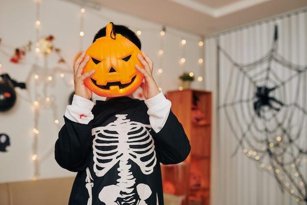Мальчик в страшном костюме на хеллоуин прячет лицо за пластиковым фонарем jack o