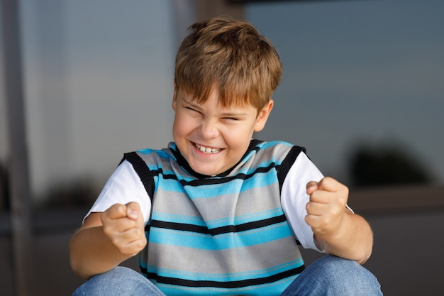 줄무늬 스웨터를 입은 소년이 주먹을 움켜 쥐는 계단에 앉아있다.