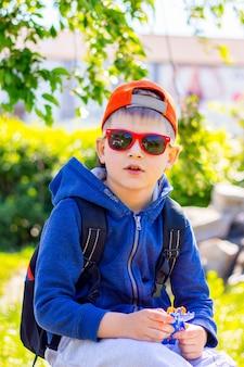 サングラスとバックパックを身に着けたスタイリッシュな服を着た男の子は、旅行中に休憩します。魅力的なファッショナブルな男の子の肖像画