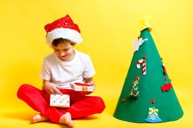Мальчик в костюме шляпы деды морозы на желтой стене. концепция рождественских и новогодних праздников
