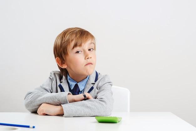 机に座っているスーツの少年。若いビジネスボーイは将来の職業を夢見ています。教育の概念。ビジネスのための新しいスタートアップ。新しいアイデアを考えている若い学生。