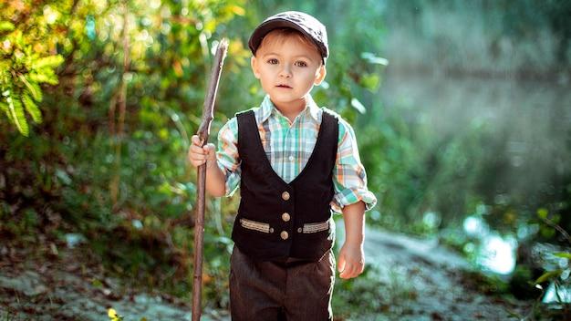 Мальчик в лесу с палкой