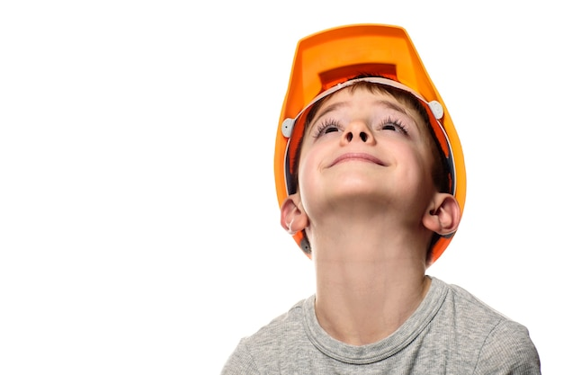Мальчик в оранжевом строительном шлеме поднял голову. портрет, лицо. изолировать на белом фоне.