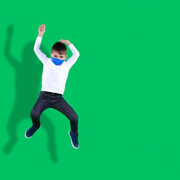 학교에 있는 소년은 쉬는 시간에 섬유 마스크를 만들고 녹색 배경에 점프하는 소년의 학교 사진