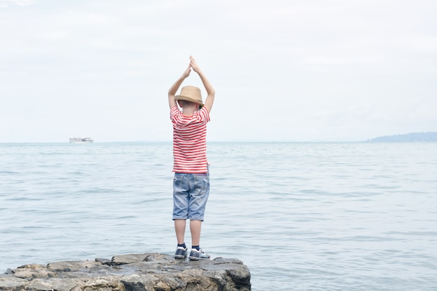 ストライプのtシャツとサングラスが石の上に立っている少年。手を挙げて、海の景色。